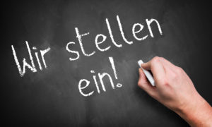 hand writing 'We are hiring!' in German on a chalkboard